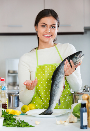 Attractive Young brunette girl preparing trout dish for healthy dinner