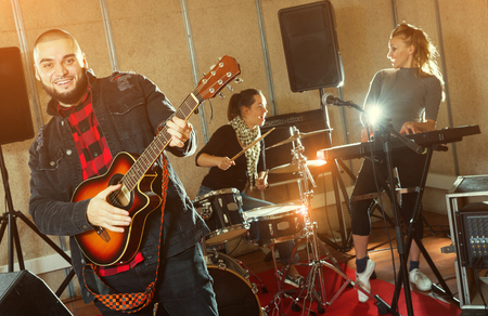 Emotional guy with guitar rehearsing with female drummer and keyboardist before  public performance Stock Photo