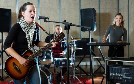 excited girl rock singer with guitar during rehearsal with male drummer and female keyboardist in studio