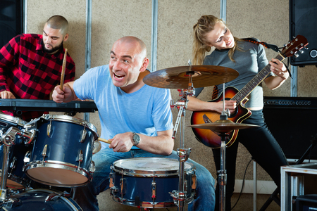 Expressive smiling glad  drummer with his bandmates practicing in rehearsal room Stock Photo