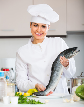 Smiling female cook preparing big fish with lemon and herbs in restaurant kitchen Stock Photo