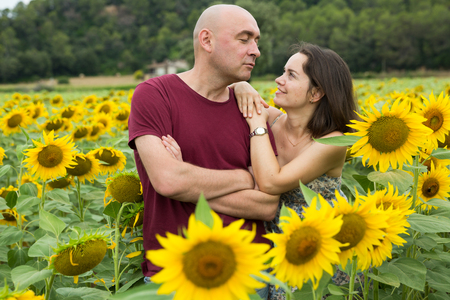 Outdoors portrait of smiling man and woman standing in field of sunflowers Stock Photo