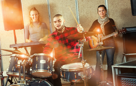 Group of young musicians with expressive male drummer rehearsing in sound studio Stockfoto