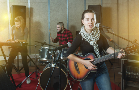 Portrait of active excited adult girl rock singer with guitar during rehearsal with male drummer and female keyboardist in studio Stock Photo