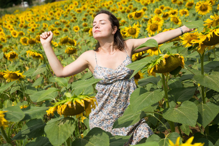 Young positive girl posing in sunflowers field and having fun