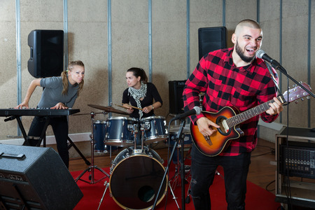 happy emotional guy with guitar rehearsing with female drummer and keyboardist before  public performance
