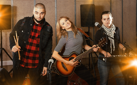 Expressive toung group of rock musicians posing with instruments in recording studio