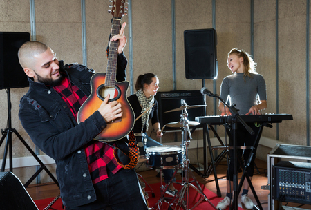 portrait of young emotional guy with guitar rehearsing with female drummer and keyboardist before  public performance Stock Photo