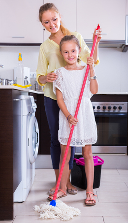 Cheerful little girl cleaning in the kitchen at home, mom helping and teaching Stock Photo