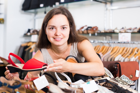 cheerful young woman choosing summer sandals in shoes store and smiling