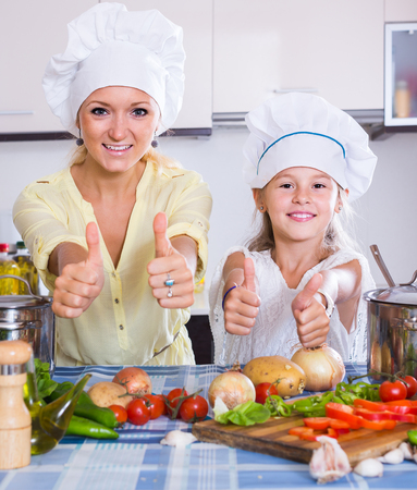 Excited spanish mom and little daughter cooking vegeterian dish indoors