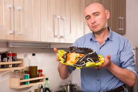 Nice man with dish of fried sturgeon with a vegetable at home kitchen