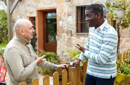 Two male farmers friendly talking outside next to wooden fence on background with brick house