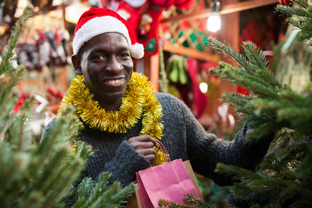 Smiling African-American guy wearing warm sweater and Santa hat choosing fir tree for New Year celebration on street fair 免版税图像