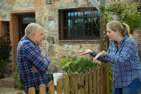 Angry woman quarreling with her male neighbor, talking through wooden fence Stok Fotoğraf