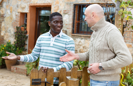 Friendly farmer greeting his neighbor, inviting to courtyard of rural house