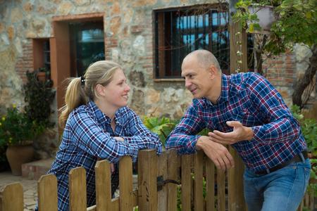 Man en vrouw communiceren op een vriendelijke manier aan de grens van hun boerderijen Stockfoto