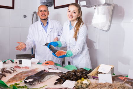 Mature american seller and young assistant offering fresh fish in shop