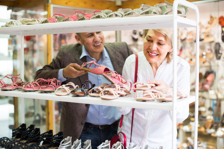 Happy smiling elderly couple picking pair of women's shoes in boutique. Focus on woman