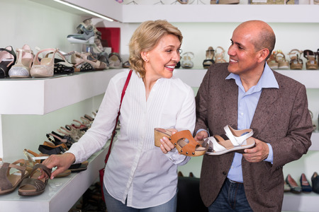 portrait of smiling senior couple picking pair of shoes in boutique. Focus on woman