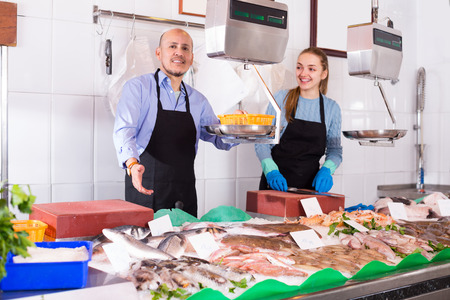 Two cheerful smiling sellers working at ordinary fish and seafood store. Focus on man
