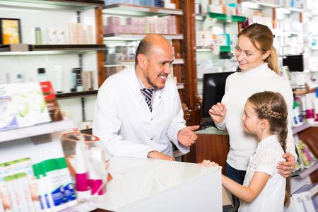 Sonriente farmacéutico varón adulto vistiendo bata blanca de pie junto a los estantes con medicamentos y ayudando a los clientes
