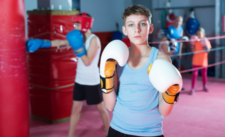 Young serious teenager with boxing gloves posing in defended stance
