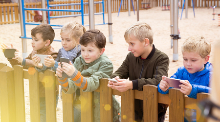 Modern kids carried away with phone spending time together outdoors in autumn day Imagens