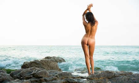Back view of sexy naked woman standing on stones at  ocean shore alone Standard-Bild
