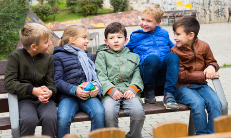 Group of cheerful children chatting while relaxing on bench on playground