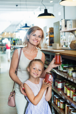 Portrait of smiling positive woman and cheerful glad girl buying conserve tomato sauce in glass jar in grocery shop Zdjęcie Seryjne