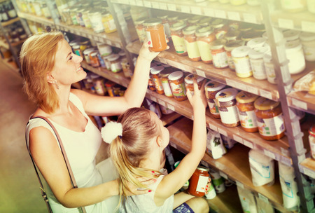 Glad young mother with daughter shopping conserve crushed tomatoes at the groceries Stok Fotoğraf