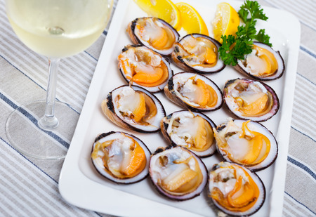 Raw bivalve mollusks (European bittersweet) served with lemon on plate Archivio Fotografico