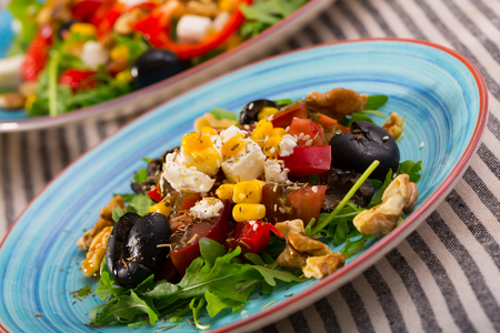 Plate with salad with Feta cheese, walnut and vegetables in restaurante. Imagens
