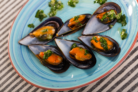 Plate with mediterranean seafood dish black shell mussels with herbs Stock Photo