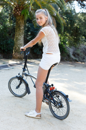 Portrait of  teenage girl sitting on  bicycle ready to go on park ride at summer day