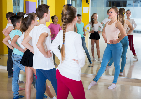 Young dance coach giving children dance class, showing movements in dance studio