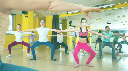 Teenage boys and girls practicing dance, stretching with female trainer in dance hall 版權商用圖片 - 115556582