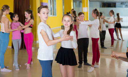Group of tweens training movements of slow foxtrot in dance studio with female coach Stockfoto