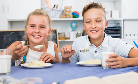 Portrait of sister with brother who are eating at time lunch at home. Banque d'images - 115556659