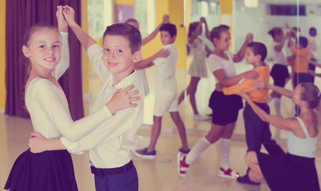 Happy children  enjoying of partner dance in class