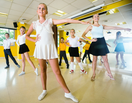 Diligent smiling positive children learn dance movements in dance class