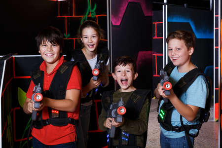 Portrait of happy excited teen kids with laser guns during lasertag game in dark room