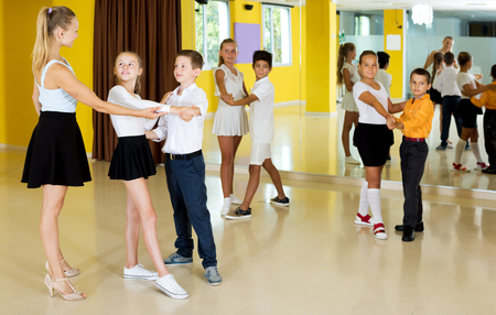 Positive children studying of partner dance  at dance school