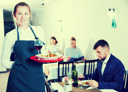Portrait of woman waiter who is standing with dish in restaurante indoor.