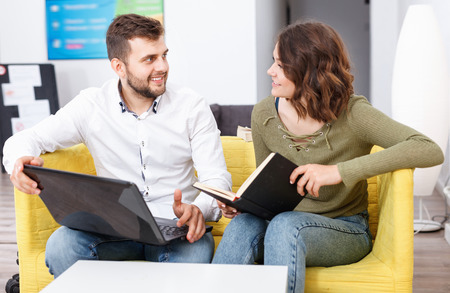 Friendly young  positive glad woman and man relaxing in cozy hostel lobby, spending time with laptop and book