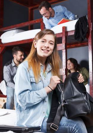 Portrait of happy girl settled in cozy modern hostel, sitting with knapsack in shared bedroom