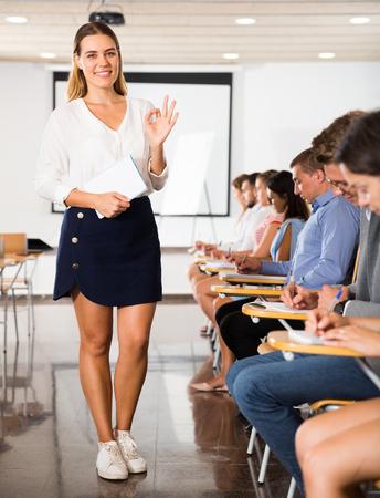 Fröhliche Studentin, die im Auditorium mit beschäftigten Gruppenkameraden ein Okay-Zeichen gestikuliert