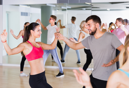 dancing couples of smiling men and women learning swing at dance class