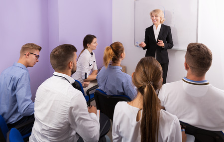 Group of glad young students attentively listening to lecture of female teacher in classroom